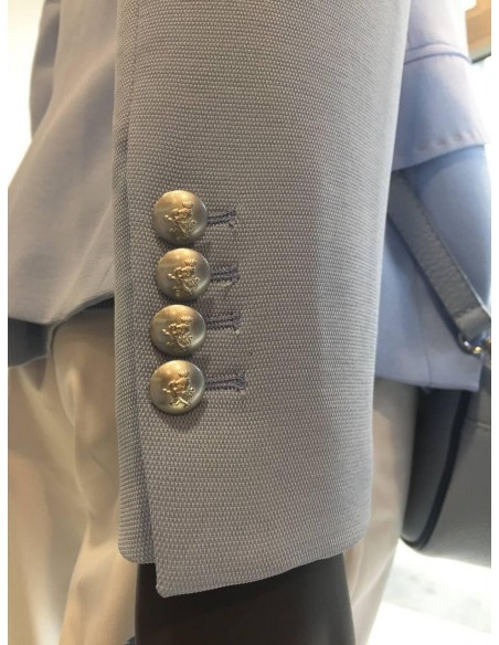 Botones en la manga con un escudo tallado.